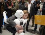 Женщина обнимает человекоподобного робота Pepper.