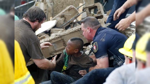 Спасатели помогают одному из пострадавших выбраться из-под руин