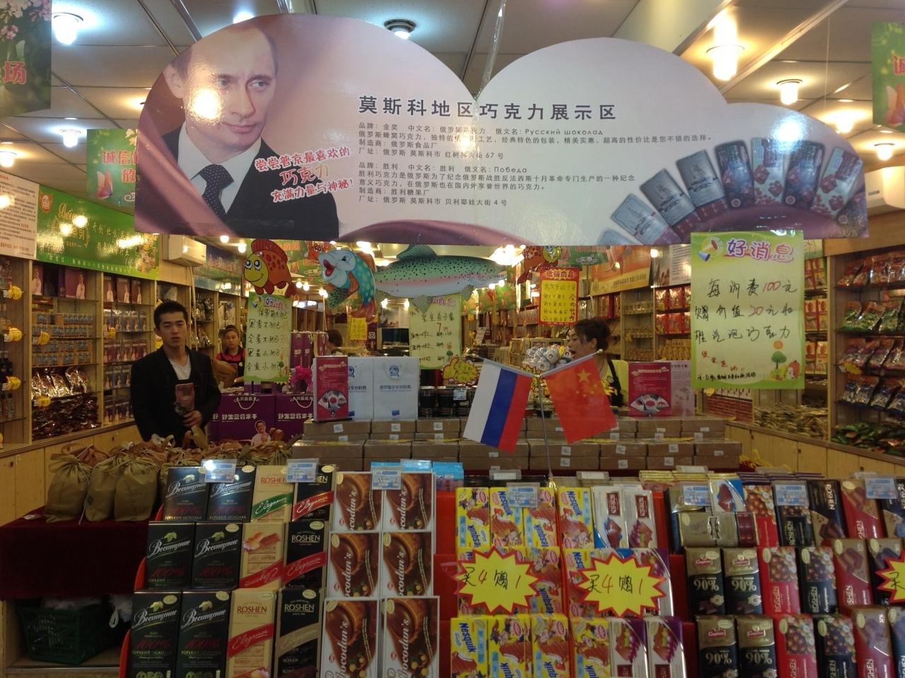 Улыбающийся Владимир Владимирович встречает китайских покупателей около стенда с шоколадом