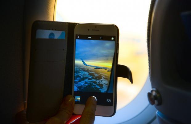 пассажир самолета фотографирует полет с телефона