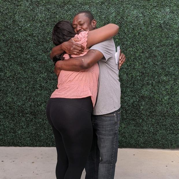 Женщина в розовой футболке обнимает мужчину