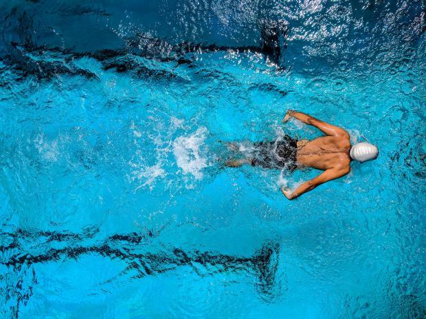 Пловец в чистой голубой воде бассейна