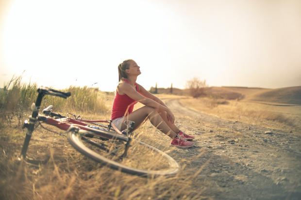 Девушка в красной майке и белых шортах сидит возле велосипеда