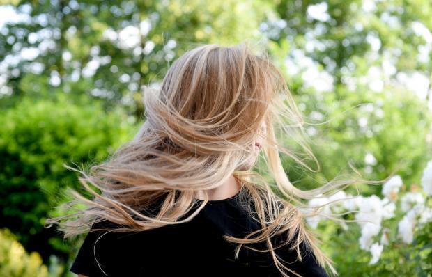 Блондинка с длинными волосами на фоне зелени