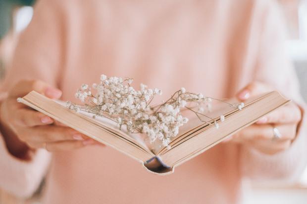 Девушка в розовой кофте с книгой и цветами в руках