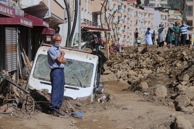 Седой мужчина стоит у затопленной машины на турецкой улице