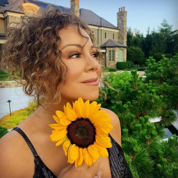 Мэрайя Кэри с желтым цветком