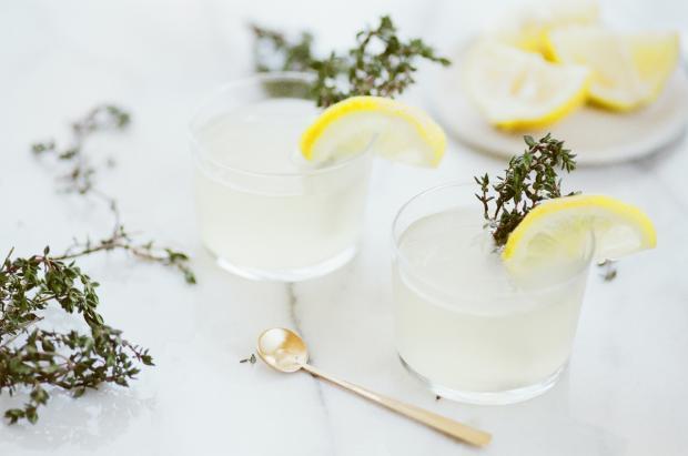 Прозрачный напиток в стакане украшенный лимоном