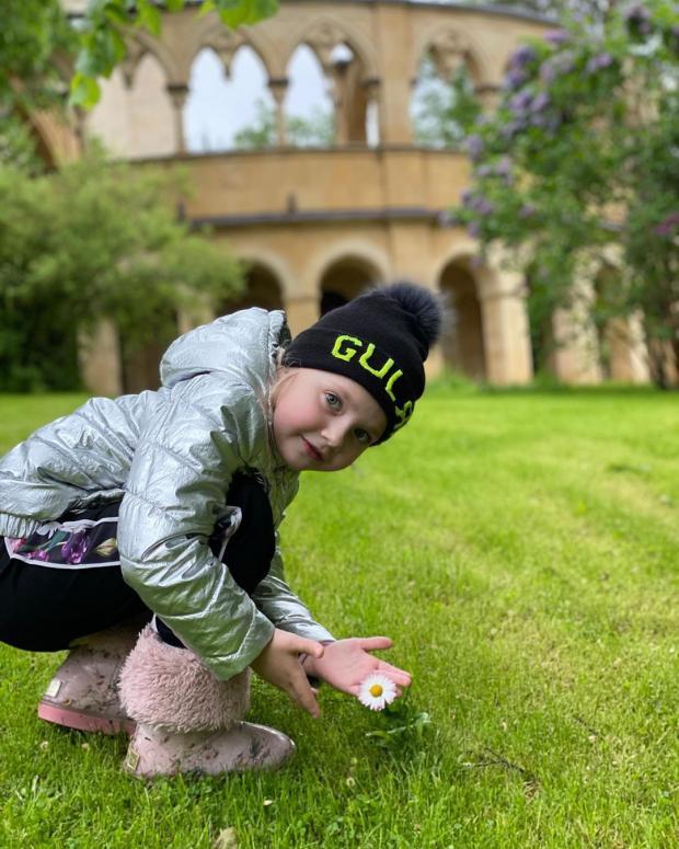Лиза Галкина в серебристой куртке во дворе дома