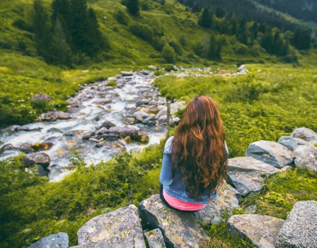 Длинноволосая девушка сидит у горной реки