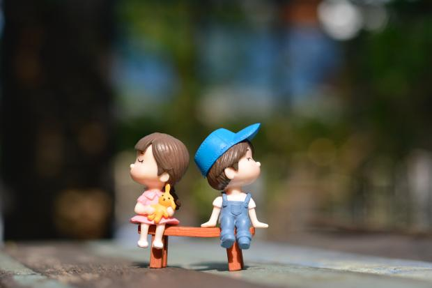 Две куклы сидят на маленькой скамейке