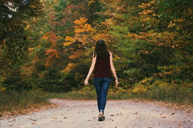 Девушка с длинными волосами идет по лесной дороге