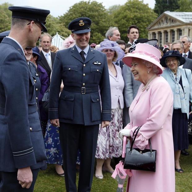 Королева Великобритании в розовом наряде разговаривает с военными