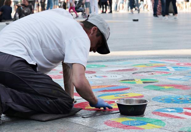 мужчина рисует на асфальте