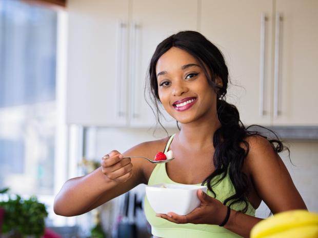 Темноволосая девушка на кухне ест из белой миски