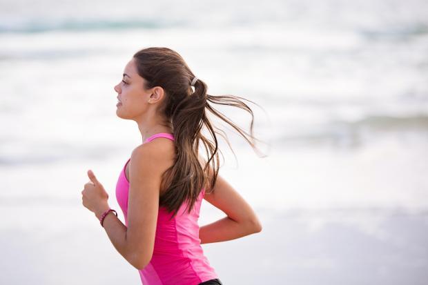 Девушка в розовом топе бежит по пляжу
