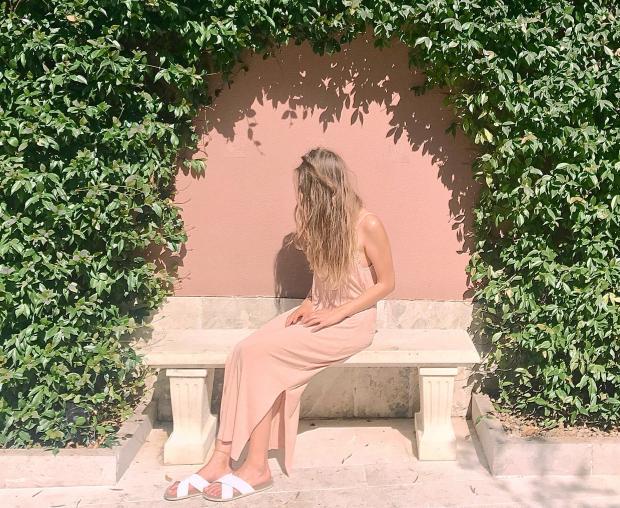 Девушка в длинном розовом платье сидит на скамейке
