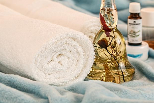 свернутые белые полотенца, ароматические масла