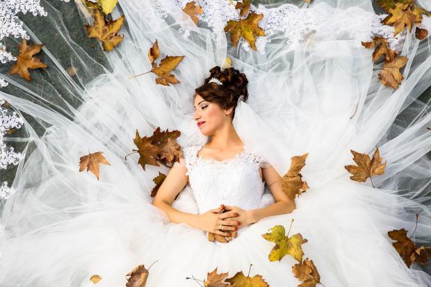 невеста лежит в осенних листьях