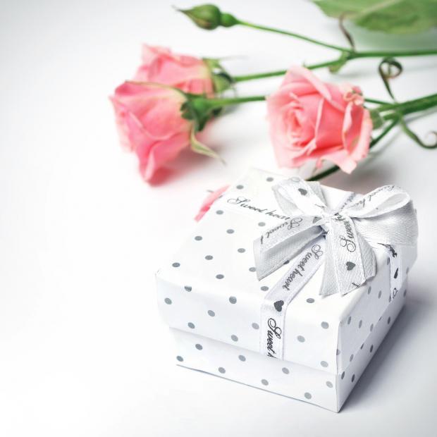 белая коробка с подарком и розовые розы