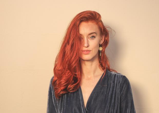 Девушка с длинными рыжими волосами на фоне персиковой стены