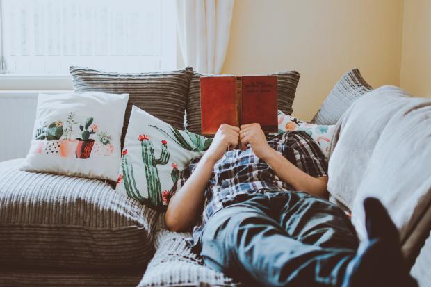 Мужчина читает книгу лежа на диване