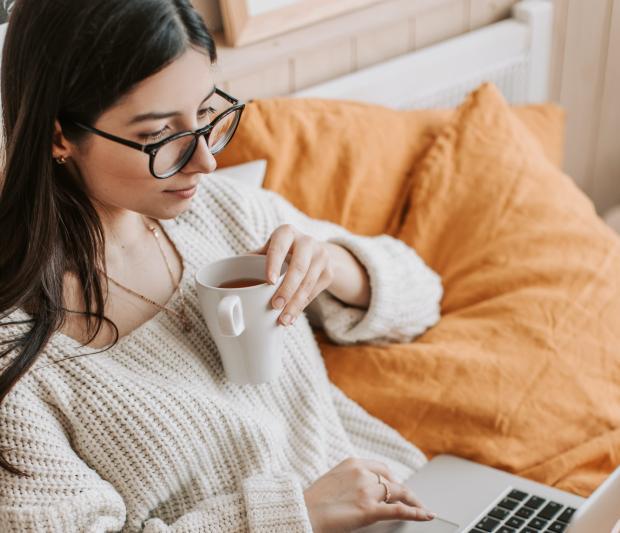 Девушка с ноутбуком и чашкой чая в кровати
