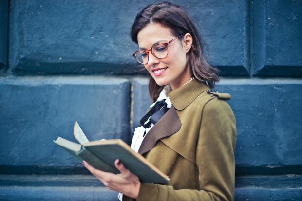 Девушка в очках и плаще стоит у синей стены