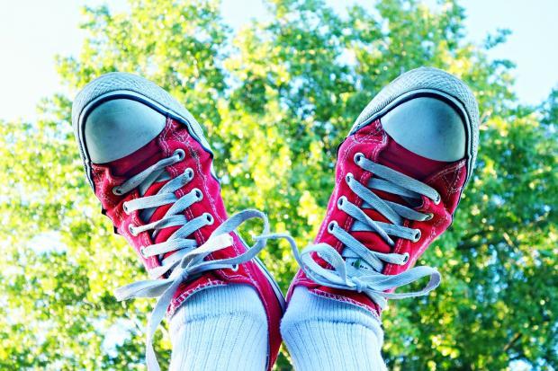 поднятые вверх ноги в красных кедах на фоне зелени