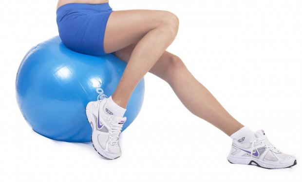 девушка в белых кроссовках сидит на мяче