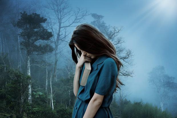 печальная девушка в синем платье на фоне голубого неба