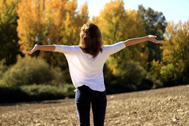девушка стоит раскинув руки на фоне осеннего леса