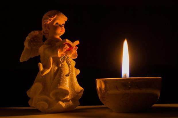 фигурка ангела перед горящей свечой