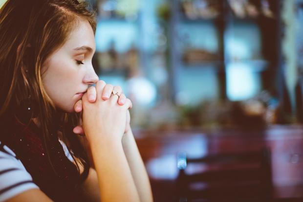 молодая девушка молится