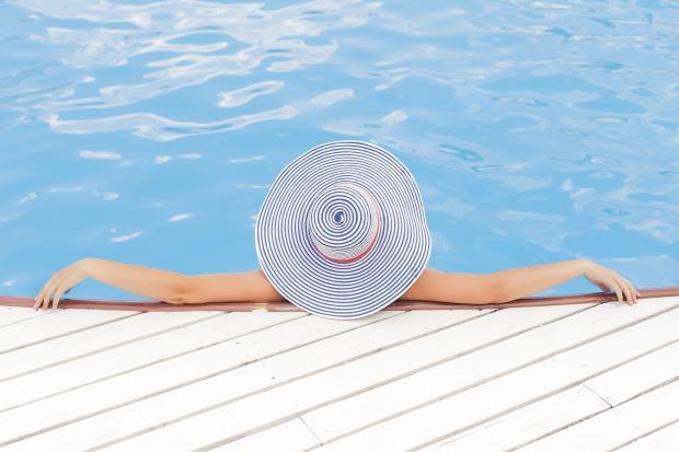 девушка в широкополой шляпе у воды
