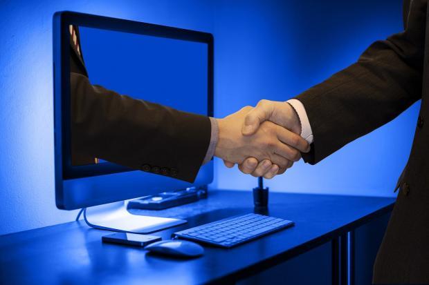 рукопожатие через экран монитора компьютера