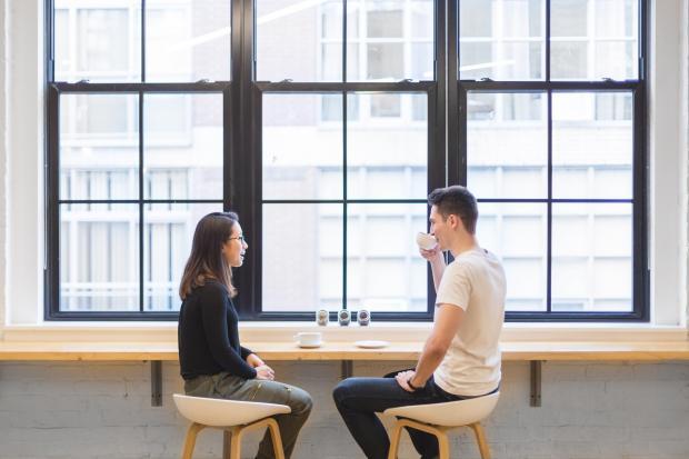 парень и девушка пьют кофе у окна