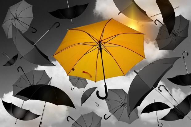 яркий желтый зонт на фоне серого неба и серых зонтиков