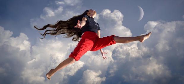 девушка с распущенными волосами прыгает по облакам