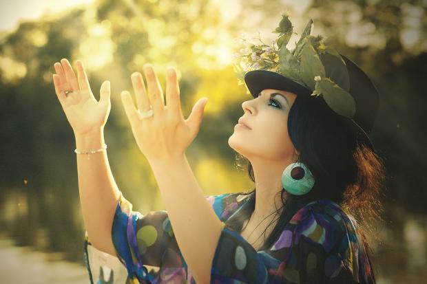 красивая женщина с крупными голубыми серьгами обращается к небу