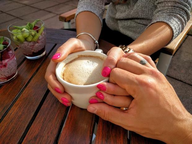 руки влюбленных держат чашечку кофе