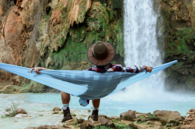 молодой человек сидит в гамаке напротив водопада