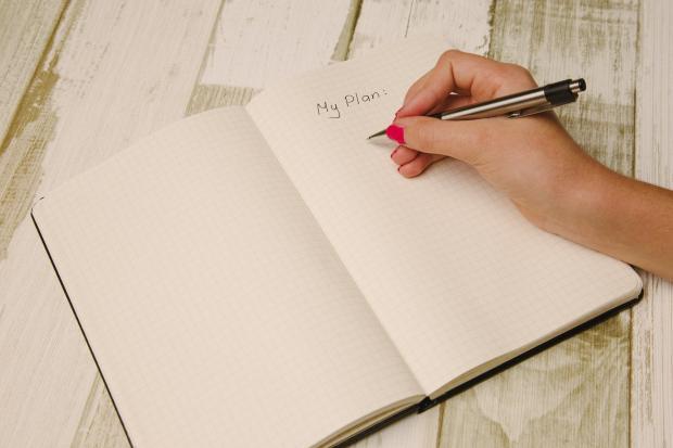 блокнот с написанным словом план, рука девушки с ручкой
