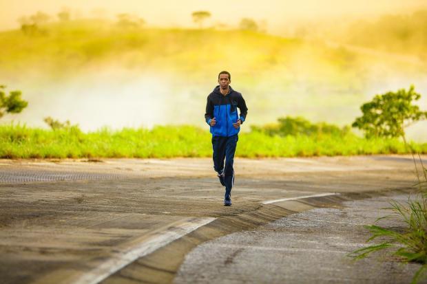 молодой человек бежит по дороге