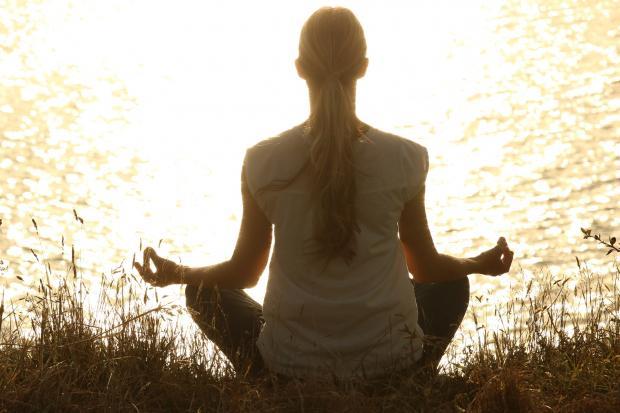 девушка медитирует на берегу реки