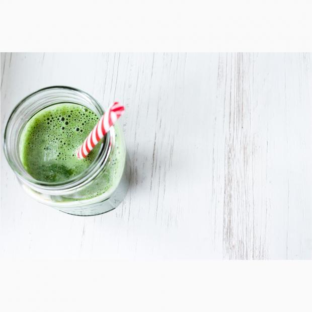 зеленый сок в стакане с полосатой трубочкой
