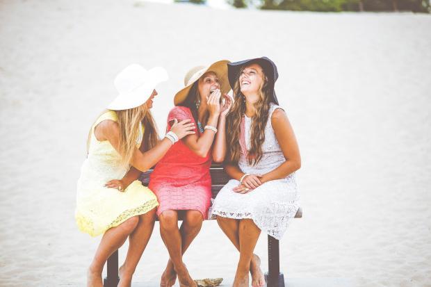 три девушки смеются, сидя на скамейке