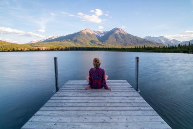 девушка сидит на речном пирсе