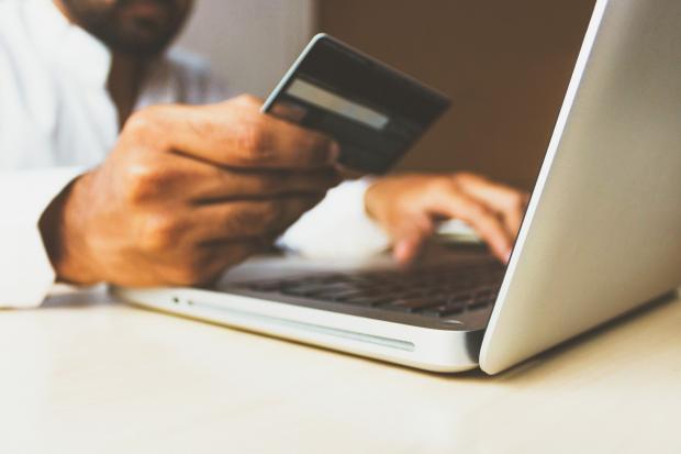 ноутбук, банковская карта в руке