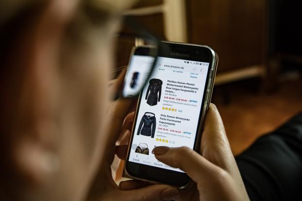 девушка со смартфоном смотрит одежду в интернет-магазине